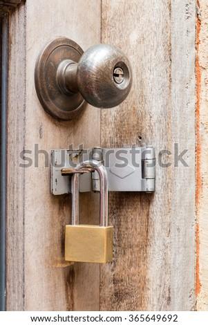 Close up rusty old door knob and padlocks on wooden door  - stock photo