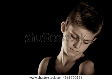 Close up Sad Face of a Boy Looking Down Isolated on Black Background with Copy Space on the Right Side. - stock photo