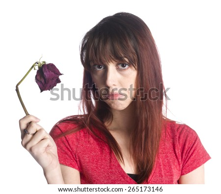 Close up Sad Young Woman in Red Shirt Holding a Dead Rose Flower While Looking at the Camera, Isolated on White Background. - stock photo