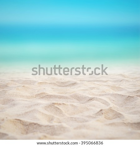 Close up sand with blurred sea sky background, summer day, copy space or for product. - stock photo