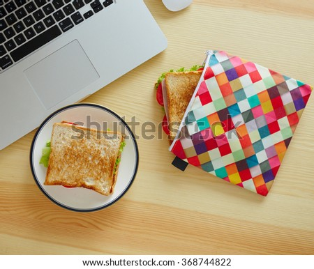 Close up sandwich in lunch bag for brunch on the table with laptop - stock photo