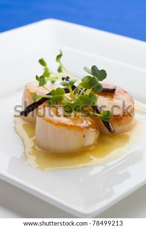 Close up Scallop seafood appetizer with vanilla stick and sauce. - stock photo