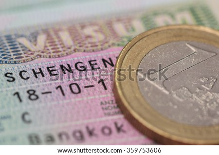 close up schengen visa in the passport with euro coin - stock photo