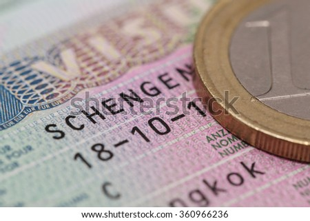 close up schengen visa in the passport with euro coin