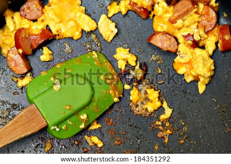 Close Up Scrambled Egg, Cheese, Sausage Leftovers in Pan. - stock photo
