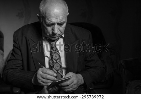 Close up Seated Old Bald Businessman Writing Some Notes on his Small Notebook with Serious Facial Expression in Monochrome Color. - stock photo