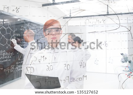 close-up  seen trough a transparent board in a chemistry lab of a beautiful student looking bored in the camera and another three analyzing information on teh background - stock photo