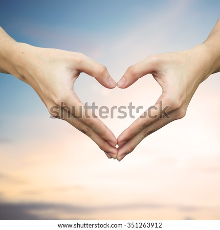 close up/selective focus on man hands make heart over blurred sunset dusk tropical  background at outdoor park:shallow man hand making heart-shape for showing healthy life:happy good healthy concept.  - stock photo
