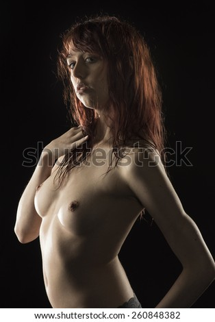 Close up Sensual Topless Young Woman Showing her Breast in Sexy Pose with her Hand on her Hair. Isolated on Black Background. - stock photo