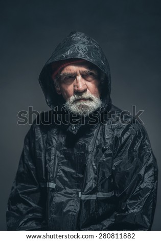 Close up Serious Adult Guy with Beard and Mustache, Wearing Black Rain Jacket, Looking at the Distance While Thinking of Something. Captured in Studio with Black Background.