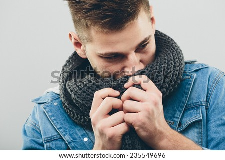 Close up Serious Handsome Young Man Wearing Denim Jacket, Thinking of Something While Smelling his Gray Knitted Scarf. Isolated on Light Gray Background.