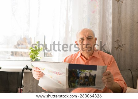 Close up Serious Senior Man Holding Tabloid Looking at the Camera While Sitting Inside his House. - stock photo