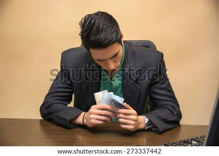Close up Serious Young Businessman, Sitting at his Worktable, Counting Cash on Hand Seriously. - stock photo