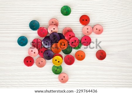 Close up sewing buttons, wood buttons, Colorful buttons, Clasper close up, buttons on white wood floor background. - stock photo
