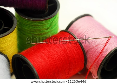 Close up sewing threads and needle on white background - stock photo