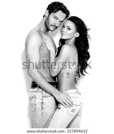 Close up Sexy Gorgeous Shirtless Couple Wearing Faded Jeans Posing Sensually on White Background While Looking at the Camera. - stock photo