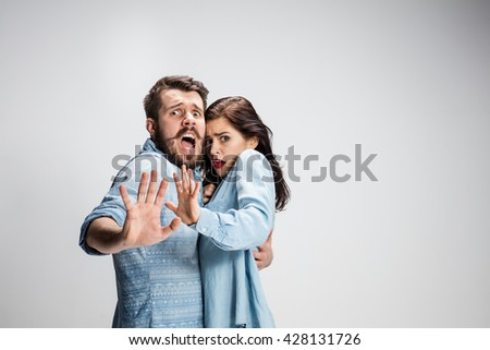 Close up Shocked Young Couple with Mouth and Eyes Wide Open Looking at Camera on gray Background. - stock photo