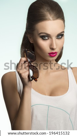 close-up shoot of sexy beautiful brunette girl with casual shirt, cool sunglasses and charming make-up  - stock photo