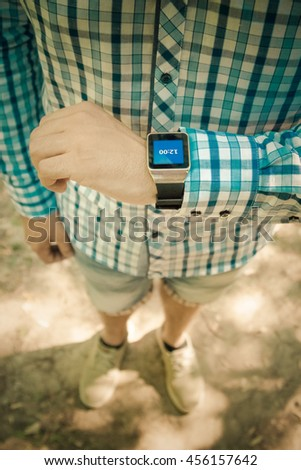 Close up shoot of young modern man checking time on smart watch display outdoors. Time, fashion and modern digital technology concepts.  - stock photo