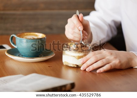 Close up shop of female hands holding a spoon and eating dessert. Young Caucasian woman having coffee while sitting at the wooden table, spending her recreation time at a cozy cafe. Selective focus - stock photo