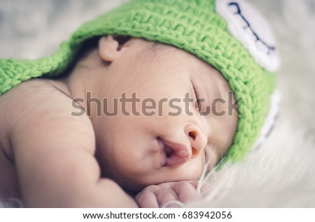 Close-up shot,cute adorable newborn baby sleeping on furry mat.motherhood and parenting concept.