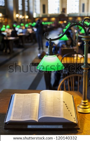 Close-up shot of a book in a busy library with boken background. - stock photo