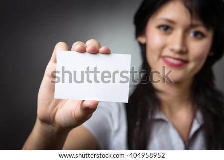 Close up shot of a businesswoman holding a blank card,  Shot in the studio on a grey background