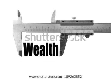 """Close up shot of a caliper measuring the word """"Wealth"""". - stock photo"""