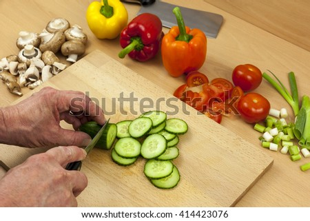 Close up shot of a chefs hands slicing an English cucumber on a wooden chopping board aside a selection of mixed cut vegetables - stock photo