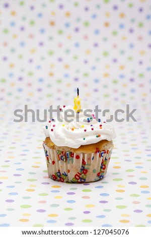 Close-up shot of a cupcake with candle isolated over polka dots background.
