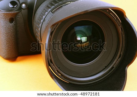 Close-up shot of a digital camera lens and body on an orange background