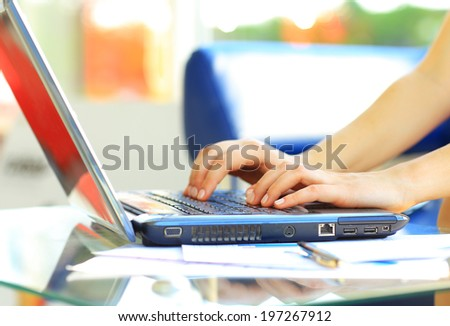 Close-up shot of a female learner typing on the laptop keyboard - stock photo