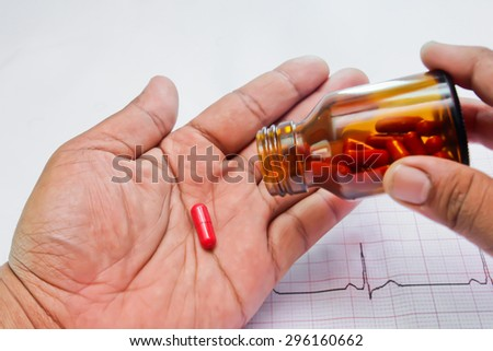 Close-up shot of a hand holding  one red pill - stock photo