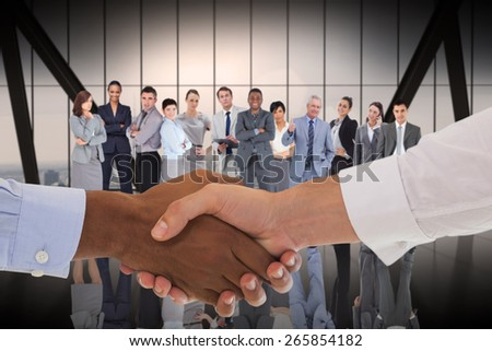 Close-up shot of a handshake in office against room with large window looking on city - stock photo