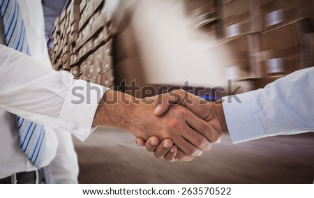 Close-up shot of a handshake in office against worker with fork pallet truck stacker in warehouse - stock photo