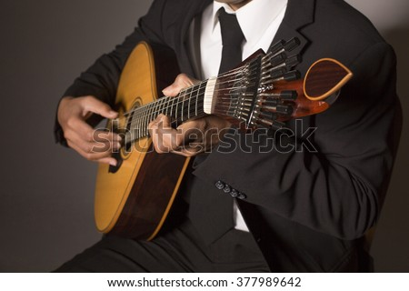 Close up shot of a man with his fingers on the frets of a portuguese guitar playing - stock photo