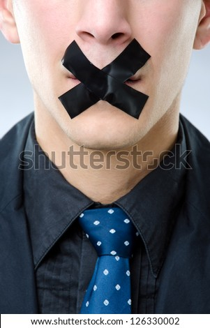 Close up shot of a man with tape over his mouth - censored speech concept - stock photo