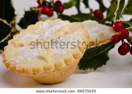 Close up shot of a mince pie with another one behind and some holly with red berries. - stock photo