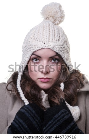 Close up shot of a model wearing a winter coat, knitted woollen, fingerless gloves and a cream bobble hat.