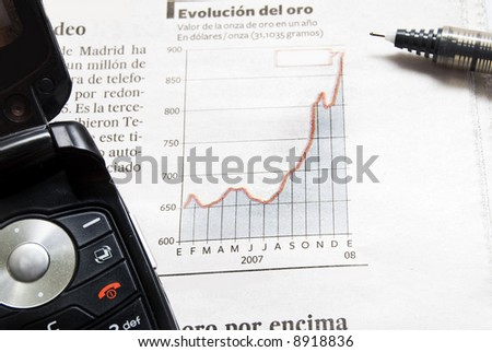 Close up shot of a pen  and phone  on stock price chart. - stock photo