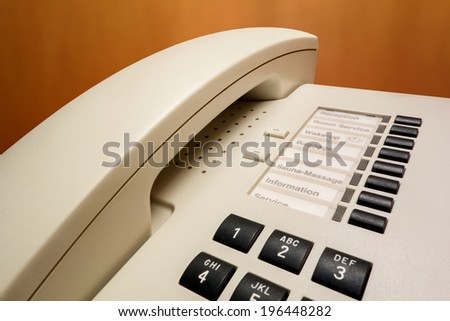 Close-up shot of a telephone receiver with buttons and texts on it in a hotel room - stock photo