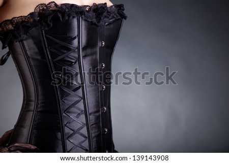 Close-up shot of a woman in black corset, with copy-space for your text