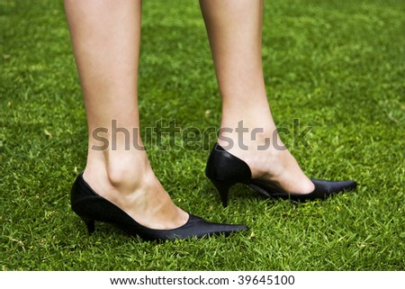 Close-up shot of a woman's beautiful legs with black high heels on green grass. - stock photo