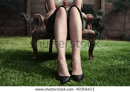 Close up shot of a woman's legs sitting on an old fashioned chair in the backyard. - stock photo