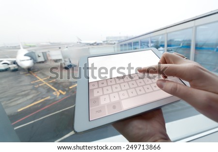 Close-up shot of a woman using touch pad with clear white screen at the airport. Boarding plane in background - stock photo