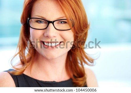 Close-up shot of a wonderful red-haired woman with a pleasant smile - stock photo