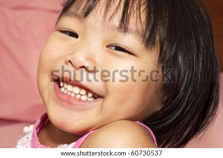 Close-up shot of a young Asian girl with smile on her face. - stock photo