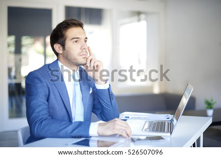 Close-up shot of a young businessman sitting at his workstation and thinking.