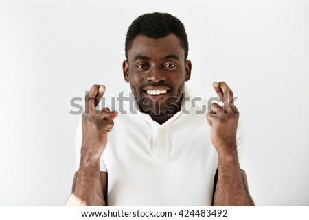 Close up shot of African man crossing fingers wishing and praying for miracle, hoping for the best, isolated against white copy space wall. Positive human emotions, expressions, feelings adnd attitude - stock photo