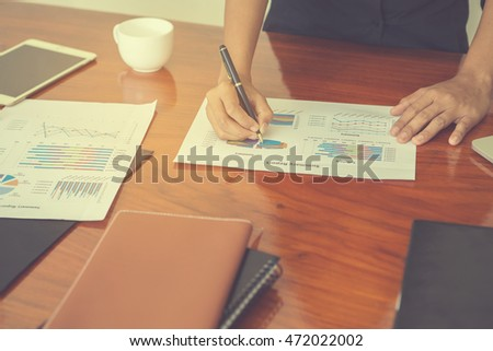 Close-up shot of an analytical working with the latest financial results Financial accounting sales forecast graphs analysis with hand writing , digital effect abstract for background